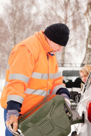 car trouble: Man filling woman car gas snow assistance winter breakdown help