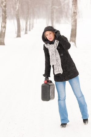 petrol can: Woman holding gas can snow car trouble winter road breakdown