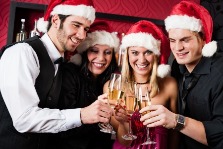 Christmas toasting party cheerful young friends with champagne at bar photo