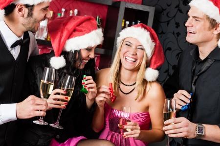fiesta amigos: La fiesta de Navidad alegre amigos en tener bebidas y diversi�n Foto de archivo