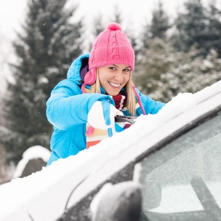 cleaning car: Limpieza de parabrisas de coche Mujer invierno nieve raspador joven feliz
