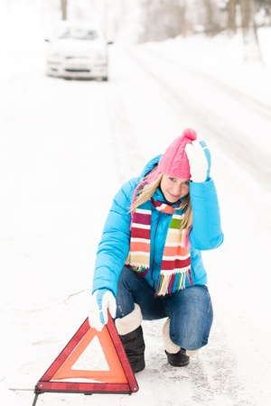 Woman putting reflector triangle car breakdown winter snow sign photo