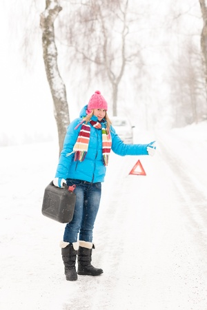 Woman hitchhiking on road snow gas can car breakdown problem photo