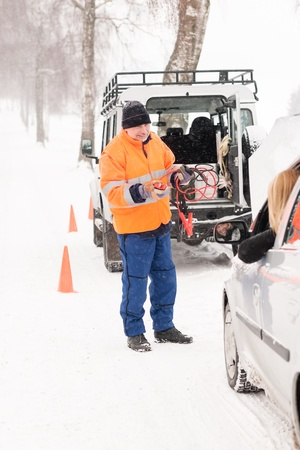 Man helping woman with broken car snow assistance winter mechanic photo