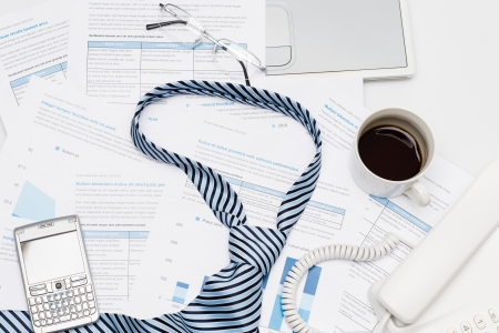 busy  office: Business tie on busy office desk paper charts, phone coffee Stock Photo
