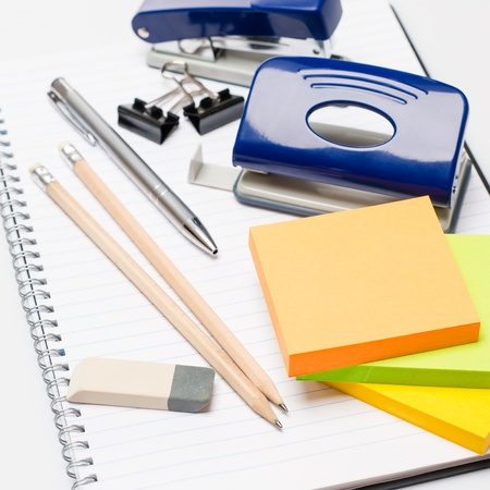 office life: Variety of business office supplies on white notepad