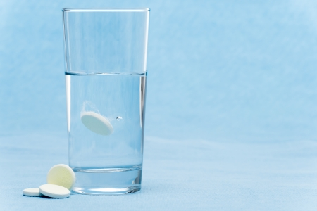 aspirin: Soluble tablet throw in water glass on blue background
