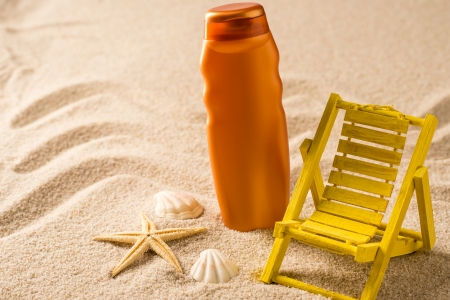 Suntan lotion container and seashells on sand holiday summer photo