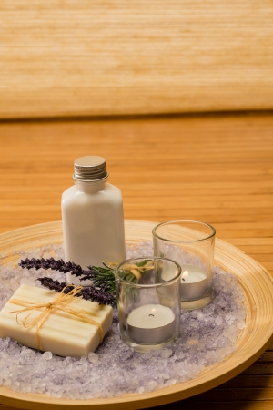 Aromatherapy lavender cosmetic products with candles on wooden tray photo