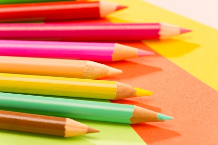 art and craft equipment: Color pencils on colorful papers close-up creativity concept Stock Photo