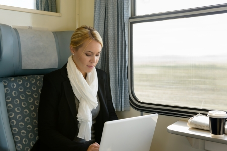 commuter train: Woman using laptop traveling by train commuter serious technology reading Stock Photo