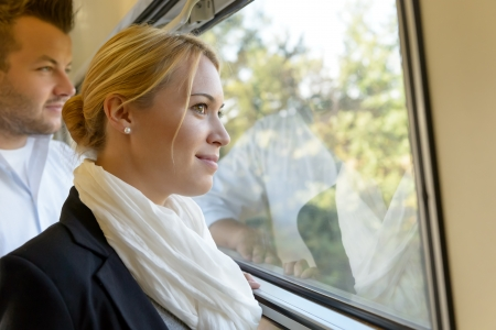contemplative: Woman man looking out the train window smiling thinking friends Stock Photo