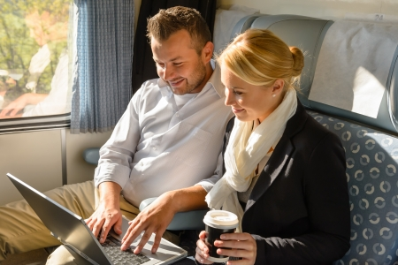 Woman and man relaxing in train laptop smiling commuters travel Stock Photo - 16968336