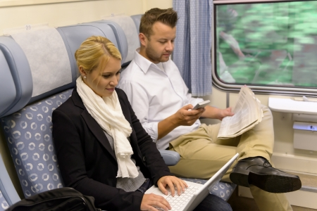 Woman with laptop man newspaper in train texting commuting reading photo