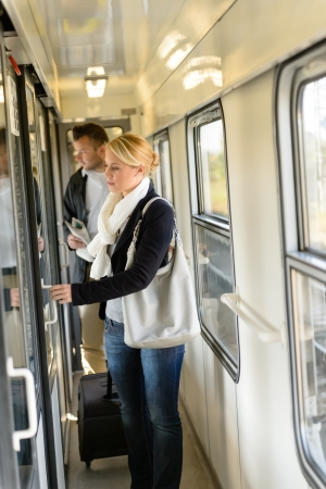 compartments: Woman opening the door of train compartment carrying luggage travel Stock Photo