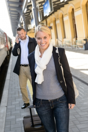 Woman in train station man on cellphone smiling commuters transport photo