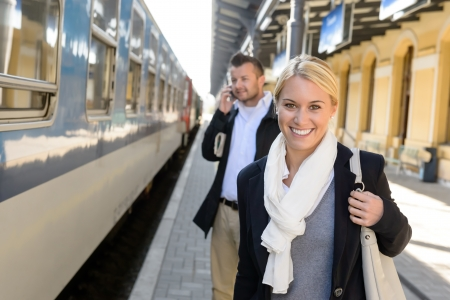 Woman smiling in train station man talking on cellphone commuters photo