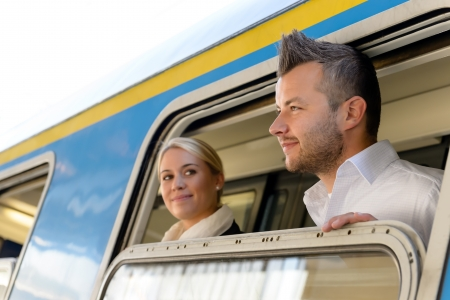 Man and woman looking out train window smiling commuters journey photo