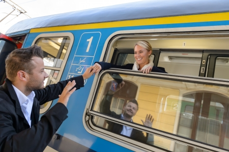 commuter: Man saying goodbye to woman on train smiling window commuter