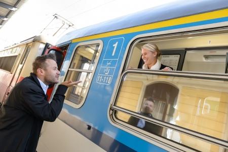 the farewell: Hombre que sopla beso a la mujer en el tren de cercanías feliz dejando Foto de archivo