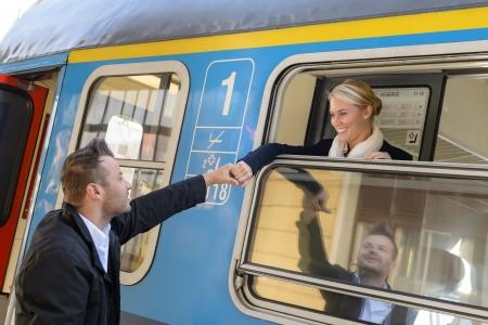 Femme laissant à l'homme le train de banlieue tenant la main en souriant au revoir