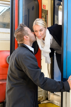 Man kissing woman goodbye on cheek train leaving friends commuter Stock Photo