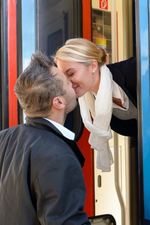 Man kissing woman goodbye train leaving romance couple commuter journey photo