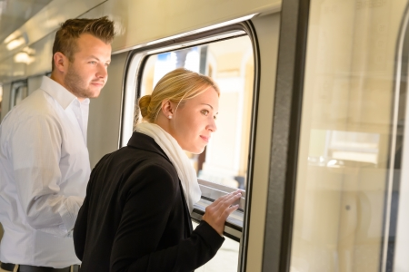 contemplative: Woman and man looking out train window smiling commuters journey
