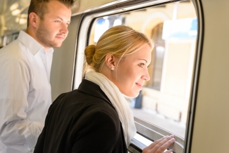 contemplative: Man and woman looking out train window smiling travel commuters