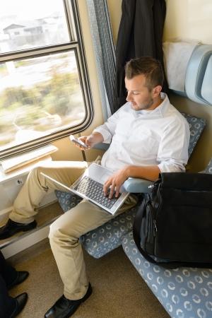 persona viajando: Hombre mensajes de texto en el tel�fono de la celebraci�n de viaje en tren de cercan�as port�til de trabajo