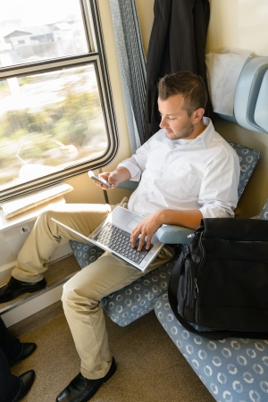 Man texting on phone holding laptop train commuter work journey photo