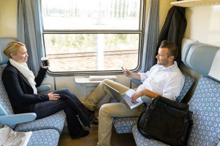 passenger vehicle: El hombre y la mujer sentada en el tren hablando sonrientes amigos de viajeros