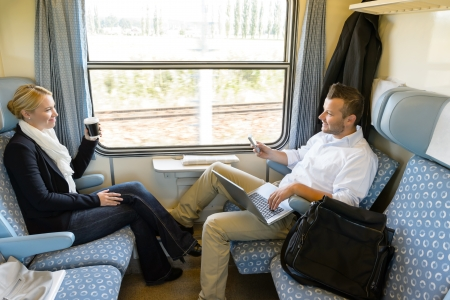 Man and woman sitting in train talking smiling commuters friends photo