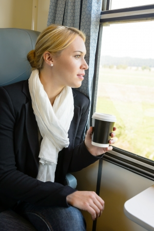 commuter train: Woman looking out the train window pensive commuter coffee trip
