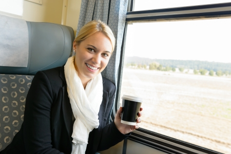 Woman smiling sitting in train holding coffee commuter travel confident Stock Photo