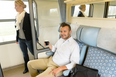 Man sitting in train woman on hallway coffee commuters smiling photo
