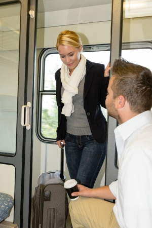 compartment: Man sitting train compartment woman getting in commuters smiling luggage