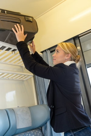 compartments: Woman putting her baggage on train grid compartment lifting commuter