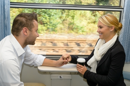 Woman and man on train holding hands sympathy friends commuters photo
