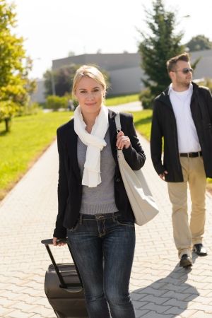 arriving: Woman arriving in park with baggage man commuter smiling journey