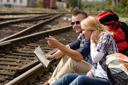 Man pointing direction with map on railroad woman happy couple photo