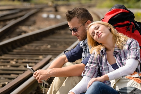 Couple backpack traveling resting on railroad map happy direction tired Stock Photo - 16968376