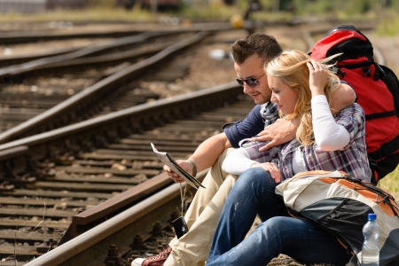 Couple looking at map sitting on railroad directions woman man Stock Photo - 16968378