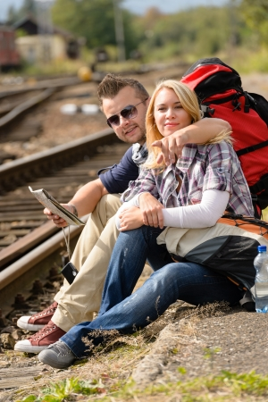 Man pointing direction to woman with map railroad vacation sitting Stock Photo - 16968369