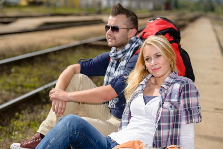 Couple backpack traveling resting on railroad trip tourists vacation togetherness photo