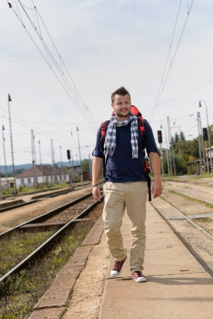 Man walking towards train station backpack travel railroad smiling tourist Stock Photo - 16968351