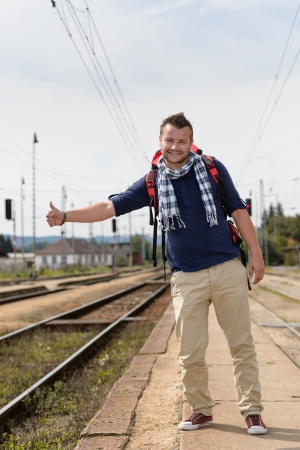 Man hitchhiking on railroad train station smiling backpack travel tourist Stock Photo - 16968337