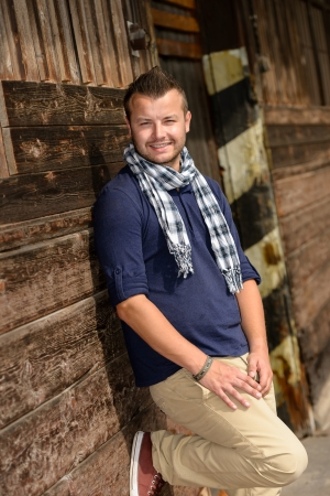 Man posing leaning against wooden wall fashion smiling lifestyle leisure Stock Photo - 16968405