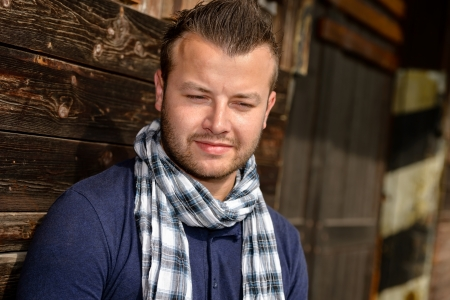 yearning: Pensive attractive man leaning against wooden wall fashion relaxing scarf