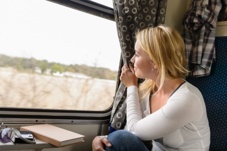 Woman train traveling looking out the window smiling vacation commuter